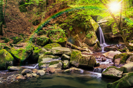 incredibly beautiful and clean little waterfall with several cascades over large stones in the forest under rainbow comes out of a huge rock covered with moss Stock Photo
