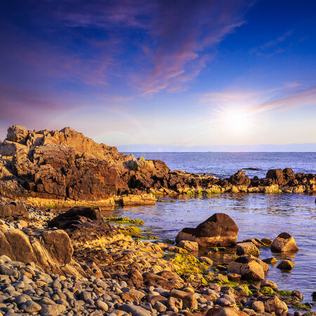 sea wave attacks the boulders and is broken about them at sunset Stock Photo