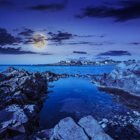 sea coast  with giant boulders against the old city at night in moon light photo