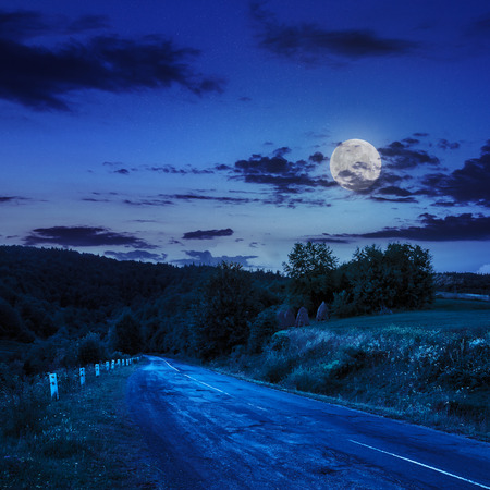 asphalt road going to mountain, passes rural places at night in moon light