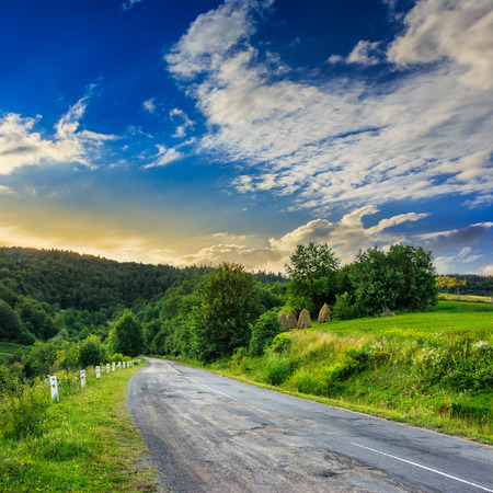asphalt road going to mountain, passes rural places