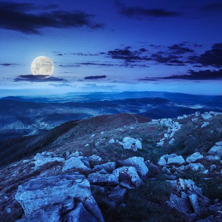 white sharp stones on the hillside at night in moon light