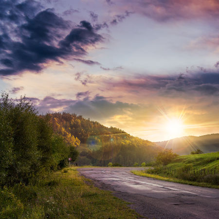 asphalt road going to mountain, passes rural places at sunset Stock Photo