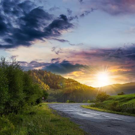 going places: asphalt road going to mountain, passes rural places at ominous sunset after the rain