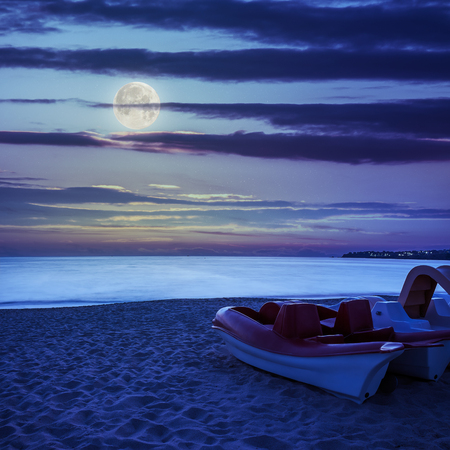 calm sea waves touch  sandy beach with few boats at night in moon light photo