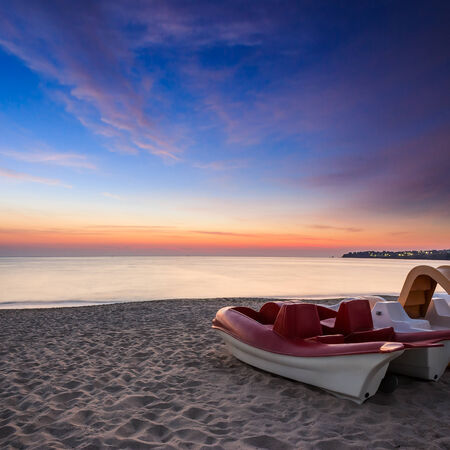 calm sea waves touch  sandy beach with few boats at sunrise Stock Photo
