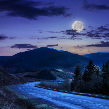 asphalt road going off into the mountain passes through the green shaded forest near rural places at night in moon light