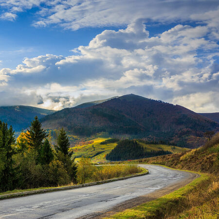 going places: asphalt road going off into the mountain passes through the green shaded forest near rural places Stock Photo