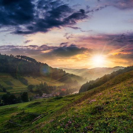 cold morning fog on a hillside meadow near mountain village at sunset Stock Photo