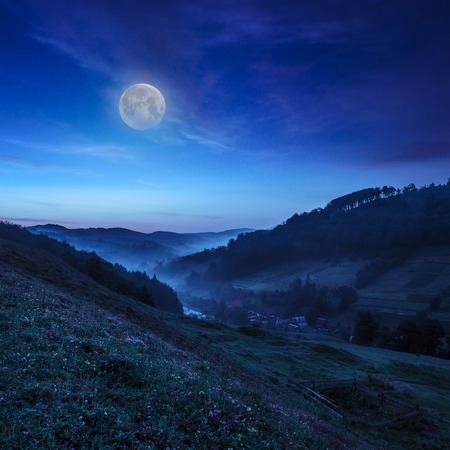 cold morning fog on a hillside meadow near mountain village at night in moon light Stock Photo