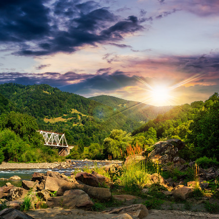 metall blidge over mountain river with stones and moss in the forest near the mountain slope at sunset Stock Photo