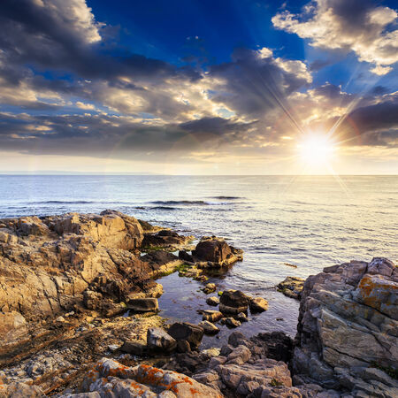 calm sea with fiev waves on coast with  boulders and seaweed at sunset Stock Photo