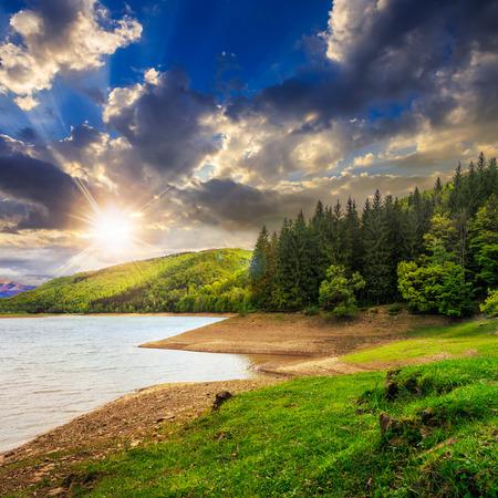 山背景にいくつか松 treesat 夕日と湖、森の近くに表示します。