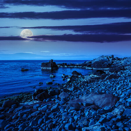 calm sea wave wash  boulders on rocky shore at night in moon light Stock Photo