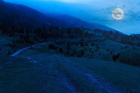 road winding in mountains under cloud fog at night in moon light