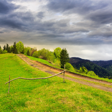 summer landscape. fence near the meadow path going up on the hillside. forest in fog on the mountain on dull cloudy day