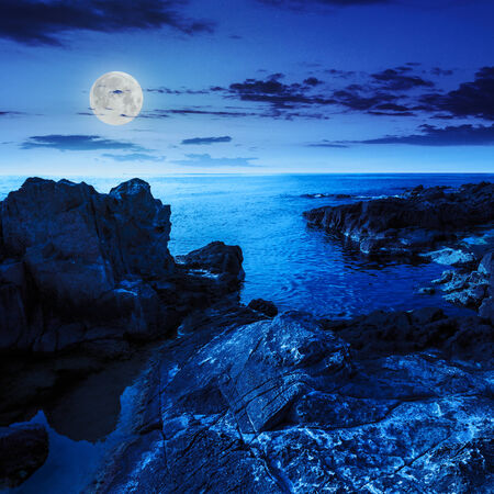calm sea wave touch giant boulders on rocky shore at night in moon light