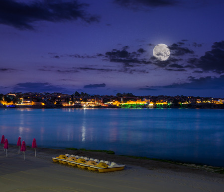 calm sea wave on city beach with clubs, boats and umbrella at night in moon light