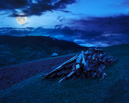 lumber and  wooden planks on agriculture field with  arable near village in mountains at night in moon light Stock Photo