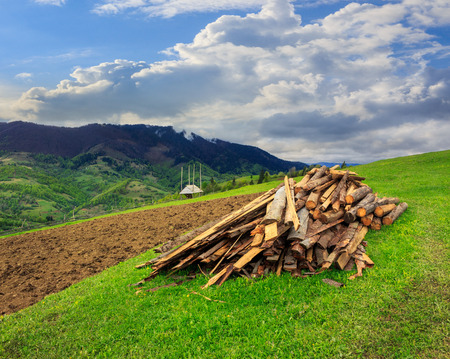 lumber and  wooden planks on agriculture field with  arable near village in mountains