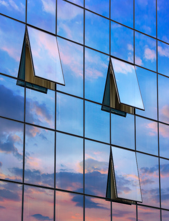 wall glass skyscraper with reflection of the sky and the three open windows at sunset Stock Photo