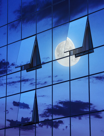 wall glass skyscraper with reflection of the sky and the three open windows at night  Stock Photo