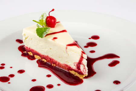 classic cheesecake in a raspberry syrup decorated with cherries and mint leaves