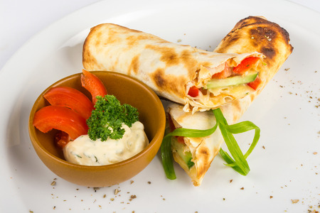 burrito with cucumber, pepper and tomato with sauce