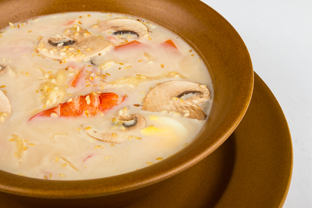 Cream soup with mushrooms champignons and shrimp sprinked with seeds in a brown dish