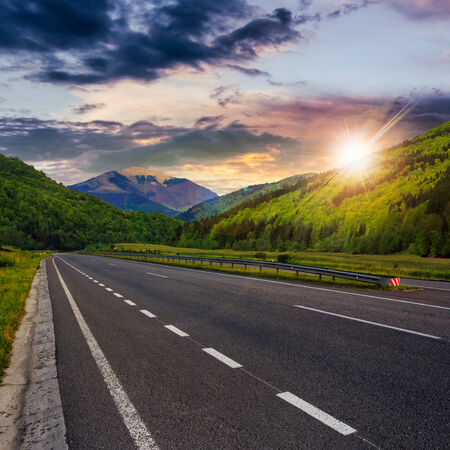 stright asphalt road in mountains passes through the green shaded forest at sunset Stock Photo