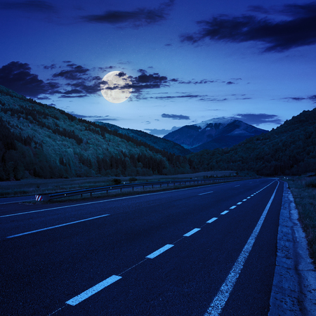 stright asphalt road in mountains passes through the green shaded forest at night in moon light