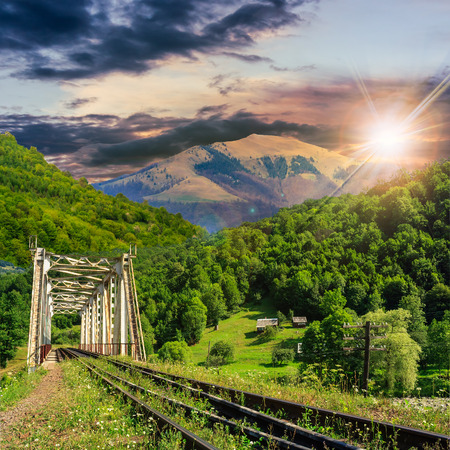 old railroad passes through the metal bridge in the mountain village at sunset