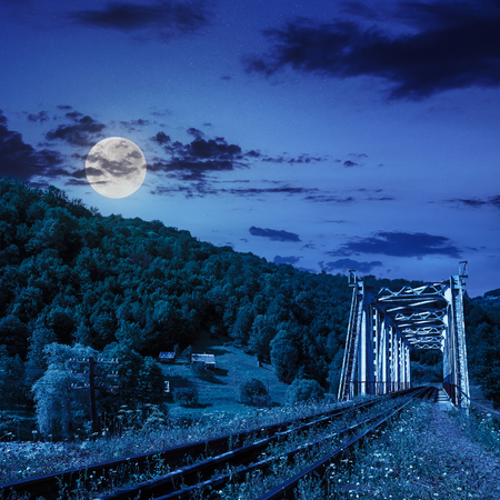 old railroad passes through the metal bridge in the mountain village at night in moon light