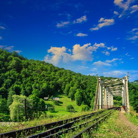 old railroad passes through the metal bridge in the mountain village Stock Photo