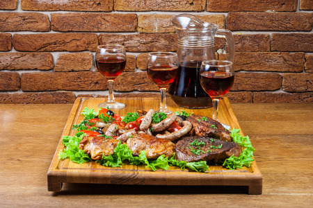 a carafe of wine and three glasses to cold cuts on a wooden board against a brick wall