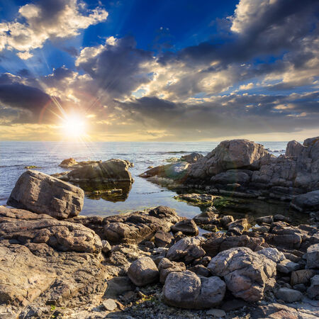 calm sea wave on rocky shore with boulders at sunset Stock Photo