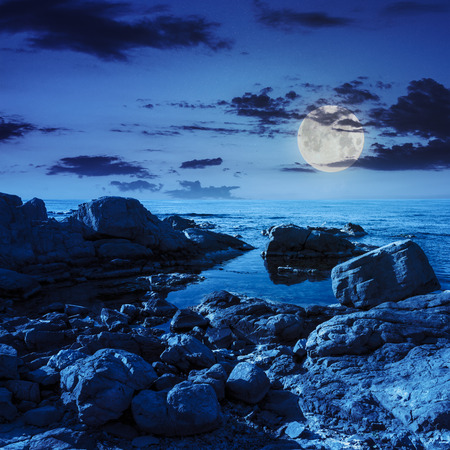 calm sea wave on rocky shore with boulders at night in moon light Stock Photo