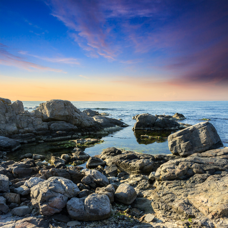 calm sea wave on rocky shore with boulders