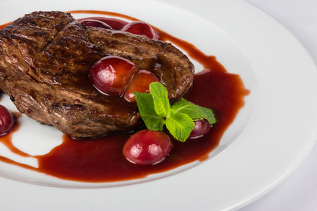 juicy grilled beef steak with plums in sauce with mint and summer taste
