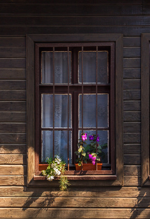 window with grate and flowers  on a wooden wall Stock Photo
