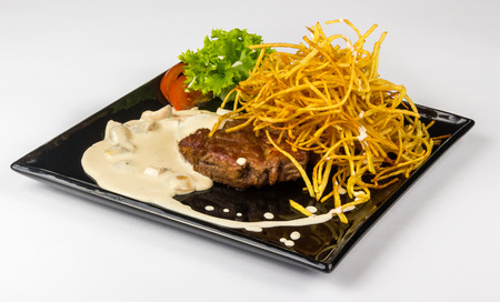 steak with potato straw, salad and tomato in mushroom sauce on black square plate