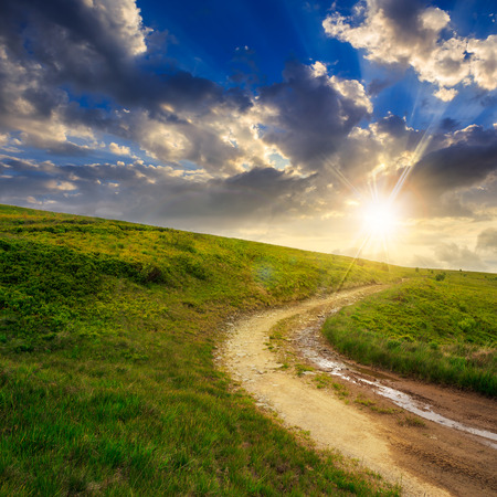summer landscape. mountain path through the field turns uphill to the sky at sunset Stock Photo - 29601401