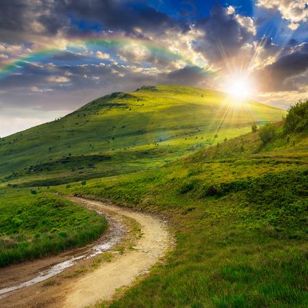 paesaggio estivo. sentiero di montagna attraverso il campo si trasforma in salita verso il cielo al tramonto con arcobaleno