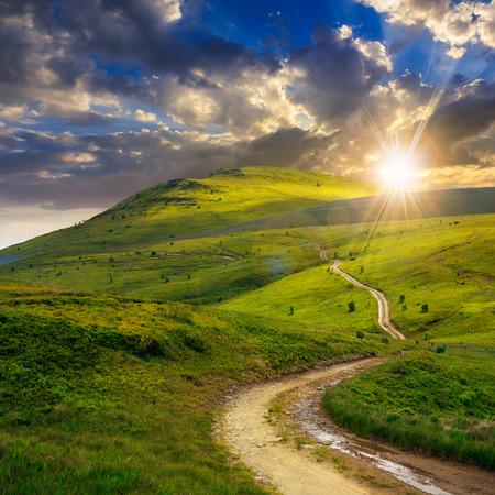 paesaggio estivo. sentiero di montagna attraverso il campo si trasforma in salita verso il cielo al tramonto Archivio Fotografico