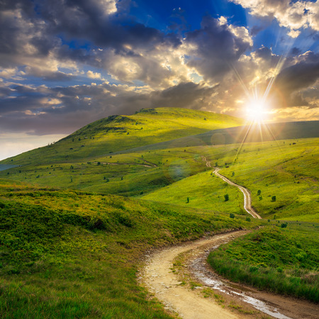 horizonte: paisaje de verano. camino de la monta�a a trav�s del campo se vuelve cuesta arriba hasta el cielo al atardecer