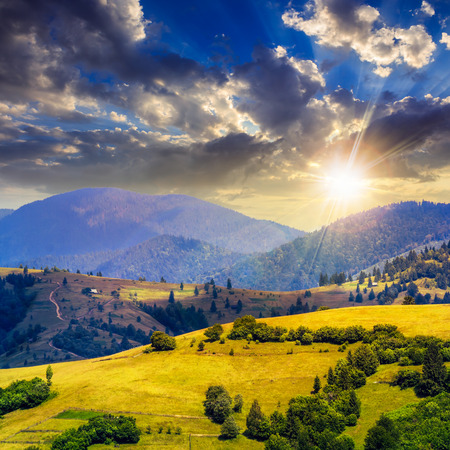 summer landscape. village on the hillside. forest on the mountain light fall on clearing on mountains at sunset photo
