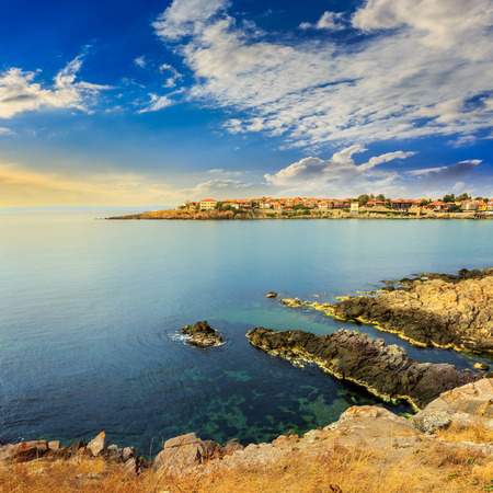 ancient european city on a rocky shore near sea in summer at sunrise