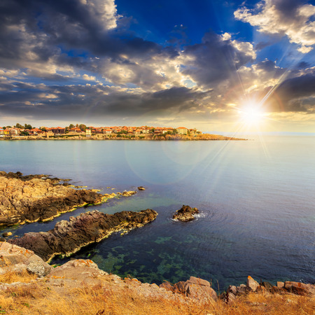 ancient european city on a rocky shore near sea in summer at sunset