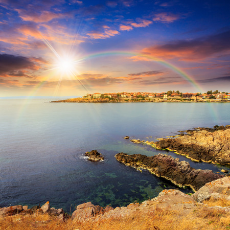 ancient european city on a rocky shore near sea in summer at sunset with rainbow