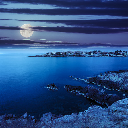 ancient european city on a rocky shore near sea in summer at night in moon light Stock Photo